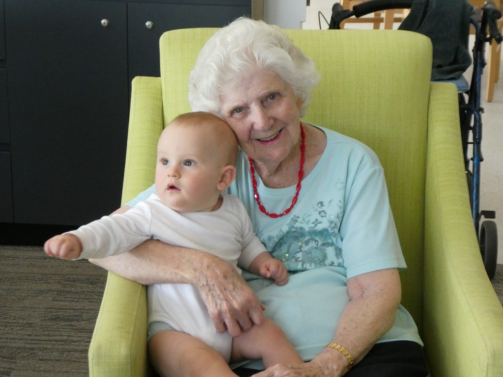 A Banksia Lodge Resident with a baby during an intergenerational playgroup